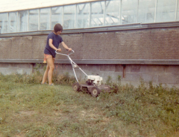 Mary mowing south side of Greenhouse - 1972.